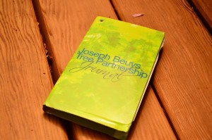 An image of a closed green Joseph Beuys Sculpture Park journal lies on a bench in the park.
