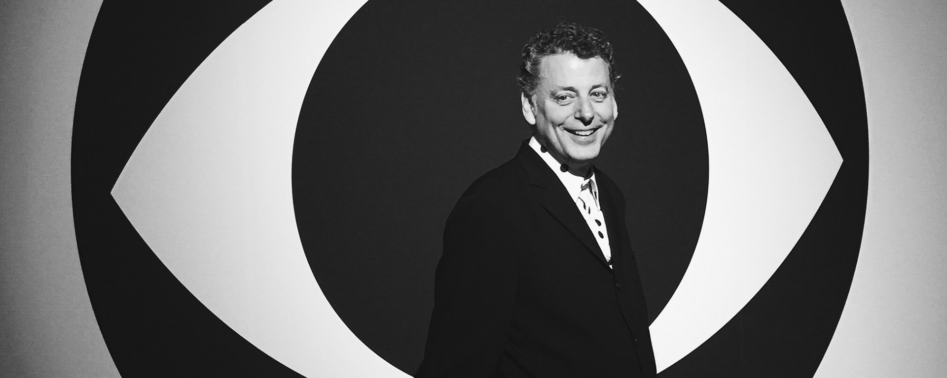Black and white photograph of Maurice Berger, Chief Curator and research professor at UMBC's Center for Art, Design and Visual Culture, standing in front of a wall with a large eye-shaped graphic in the background. Photograph by James Estrin.