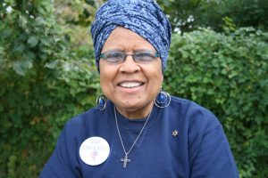 A portrait of a senior medium-dark skinned woman with a blue head wrap and blue glasses wearing a blue shirt, a large circular pin, a cross necklace, and hoop earrings. The woman is smiling and standing outside in front of greenery.