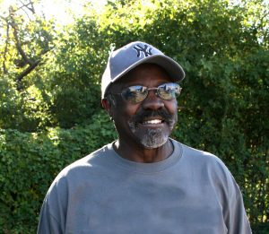 A portrait of a dark skinned man with a mustache and beard wearing a blue baseball cap, tinted glasses, and a blue shirt. The man is smiling, looking into the distance, and standing outside in front of greenery.
