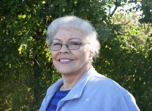 A portrait of a senior, light skinned woman with short white hair wearing thin glasses and a blue cardigan over a striped blue shirt. The woman is smiling and standing outside in front of greenery.